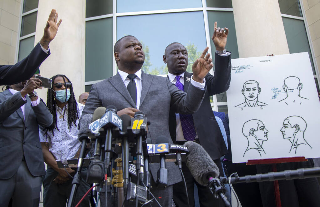 Attorneys for the family of Andrew Brown Jr., including Harry Daniels, center, and Ben Crump take questions from reporters during a press conference outside the Pasquotank County Public Safety building Tuesday, April 27, 2021 to announce results of the autopsy they commissioned, which they said showed five bullet wounds including one to the back of the head. They accused Pasquotank County officials of hiding information and keeping justice from being served in Elizabeth City.