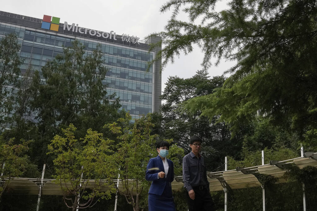 People walk through a park near the Microsoft office building in Beijing, Tuesday, July 20, 2021. The Biden administration and Western allies formally blamed China on Monday for a massive hack of Microsoft Exchange email server software and asserted that criminal hackers associated with the Chinese government have carried out ransomware and other illicit cyber operations. (AP Photo/Andy Wong)