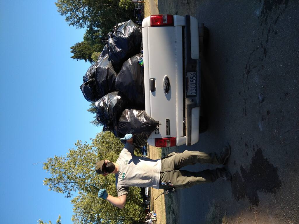 Sonoma County Regional Parks Aide Michael Stanford hauls in mounds of trash from Steelhead Beach in Forestville over the Fourth of July holiday. Photo by Jessica Saler