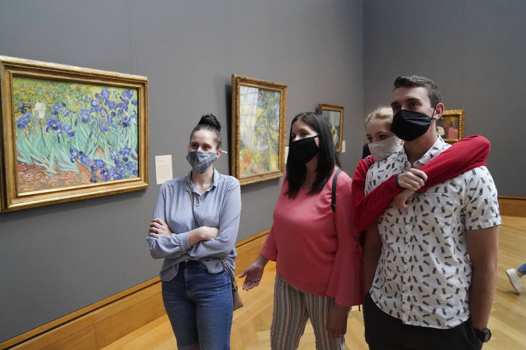 """FILE - In this Wednesday, May 26, 2021 file photo, visitors wear masks as they view art, including Vincent van Gogh's """"Irises"""", at left, at the newly re-opened Getty Center amid the COVID-19 pandemic in Los Angeles. (AP Photo/Marcio Jose Sanchez, File)"""