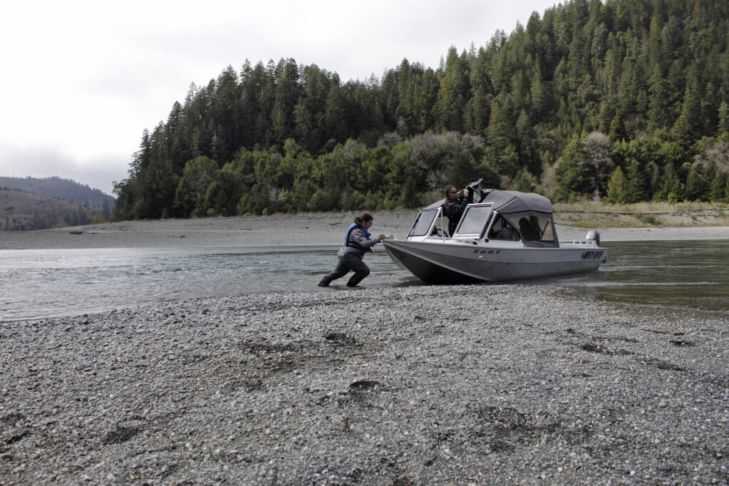 Hunter Maltz, a fish technician for the Yurok tribe, pushes a jet boat into the low water of the Klamath River at the confluence of the Klamath River and Blue Creek on March 5, 2020, as Keith Parker, as a Yurok tribal fisheries biologist, watches near Klamath in Humboldt County.  Federal officials announced Wednesday that farmers who rely on a massive irrigation project spanning the Oregon-California border will get 8% of the deliveries they need amid a severe drought. (Gillian Flaccus / Associated Press)