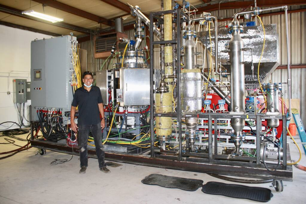 Brian Bauer, co-founder and CEO of Resynergi, Inc., based in Rohnert Park, stands next to the company's innovative plastic recycling system that can convert a ton of plastic waste per day into reusable oils, fuels and other products. (Courtesy Photo)