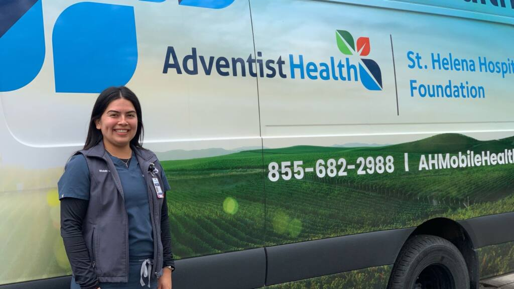 Noemi Mauricio, clinical community educator at Adventist Health St. Helena, stands next to the St. Helena Hospital Foundation mobile clinic van that has been vaccinating vineyard and winery workers in 2020-2021. (Facebook / Adventist Health St. Helena)