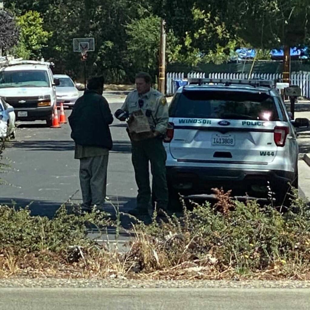 A Windsor police officer was spotted giving shoes to a man who is homeless Thursday, July 29, 2021. The officer's act of kindness is being praised on social media.   (Sonoma County Scanner Updates/Facebook)