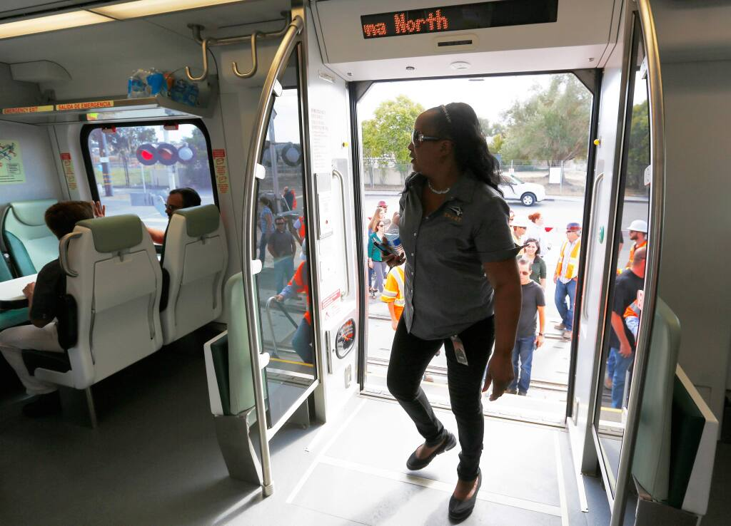 SMART administration services manager Nina West boards a SMART train for a ride over the new Petaluma River Bridge in Petaluma, California on Wednesday, October 7, 2015. (Alvin Jornada / The Press Democrat)