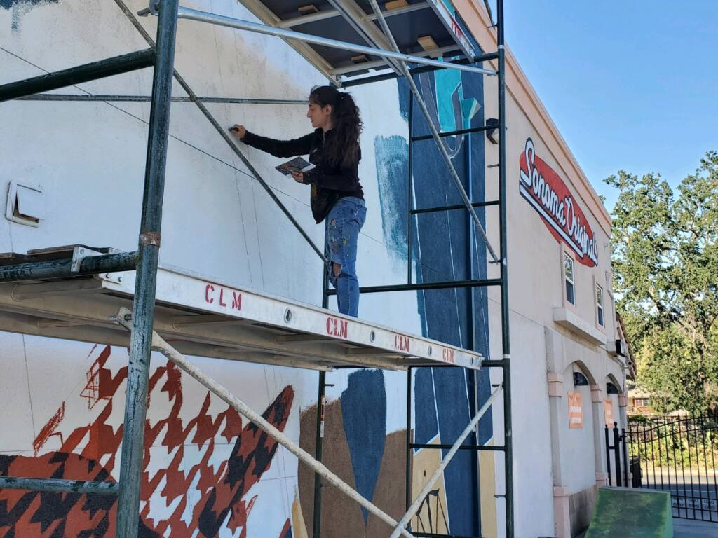 Rima Makaryan, co-founder of Sonoma County Artists Propelling Equity, works on a mural of local activist D'mitra Smith at Sonoma Originals skate shop in Boyes Hot Spring on Tuesday, June 9, 2021. (Remi Newman)