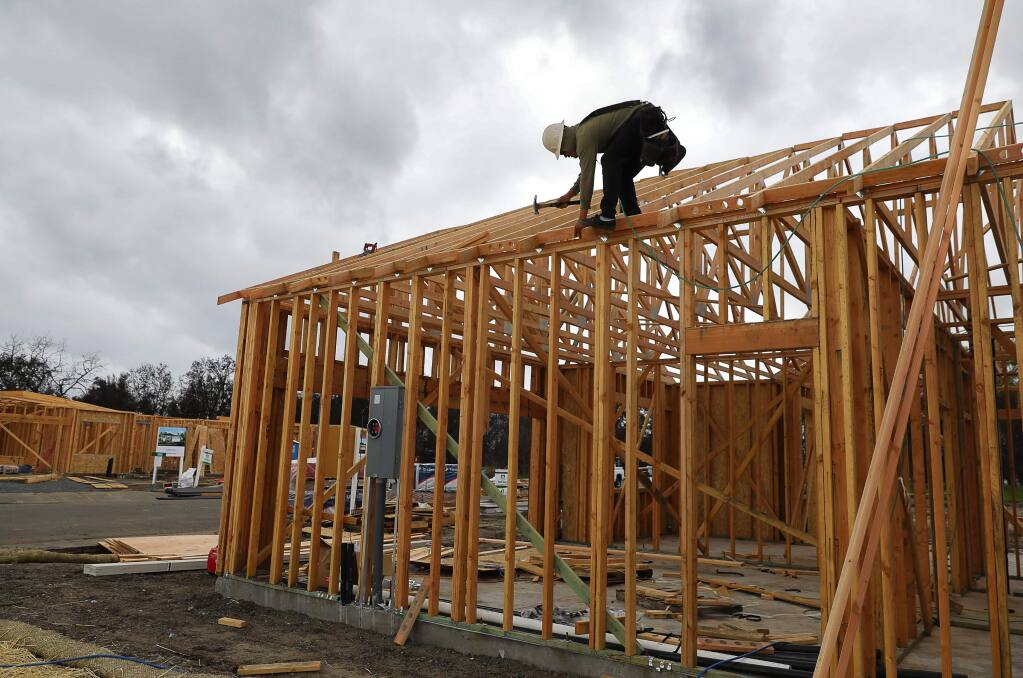 Julio Perez works on the construction of a new home on Willow Green Place, in Larkfield on Wednesday, April 11, 2018. Silvermark Construction is building several new homes on lots that were purchased after the October wildfire. (Christopher Chung/ The Press Democrat)
