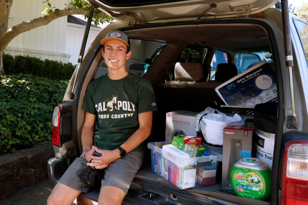 Colton Swinth sits beside some of the items he is bringing to furnish his dorm room when he starts his freshman year at Cal Poly San Luis Obispo this fall, at his home in Santa Rosa, on Thursday, July 30, 2020. (Alvin Jornada / The Press Democrat)