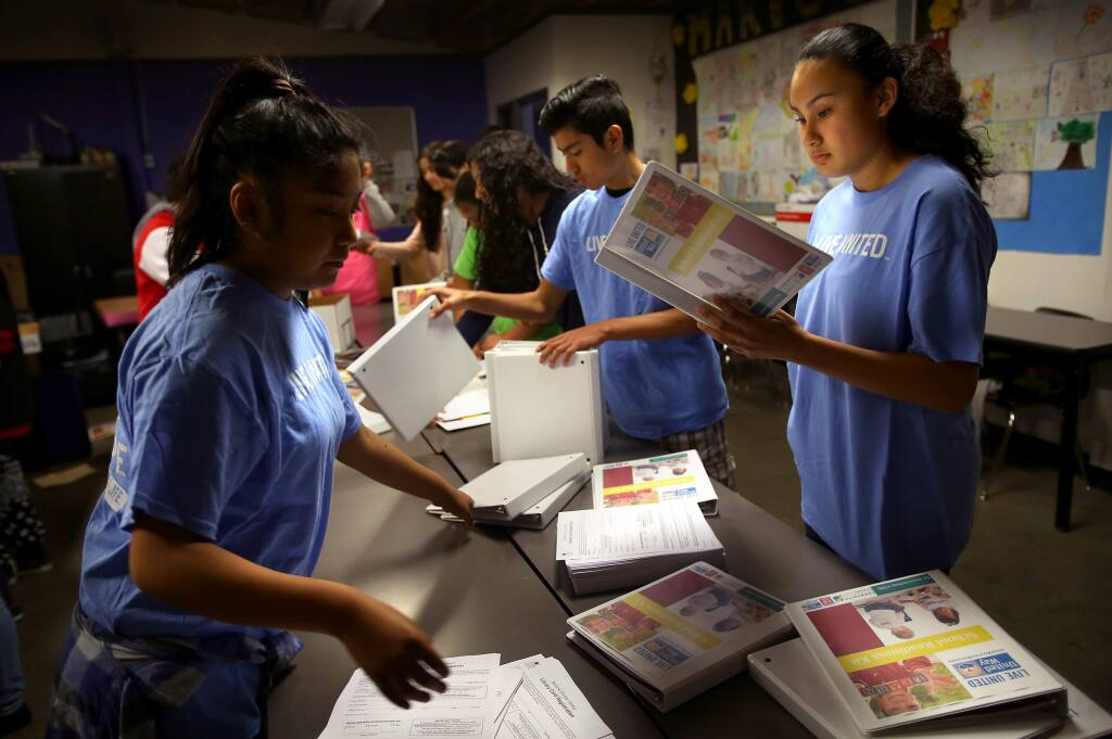 Nancy Trejo, right, Josue Lopez and Karen Hernandez put together binders for school readiness backpacks at Roseland University Prep, as part of its United Way day of service, in Santa Rosa on Wednesday, February 4, 2015. Students put together 1200 backpacks for three to four year old children.(Christopher Chung/ The Press Democrat)