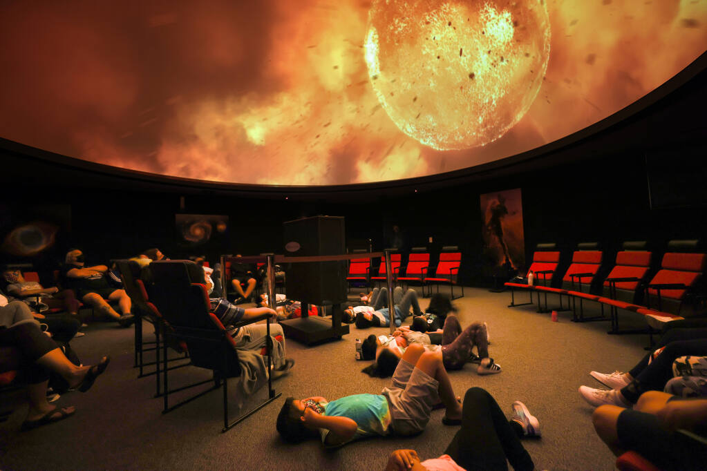 Children in Space Camp watch a movie about the universe at the SPARQ Planetarium at Piner High School in Santa Rosa on Thursday, July 29, 2021.  (Christopher Chung/ The Press Democrat)