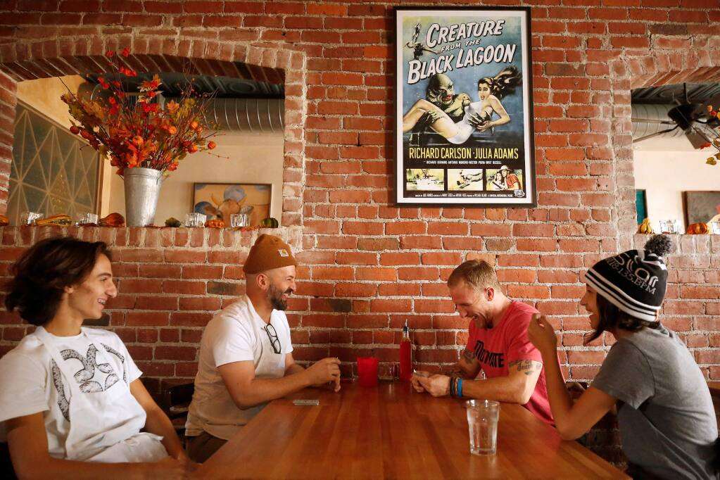 Dino Bugica, second from left, owner of Diavola Pizzeria, plays Briscola, an Italian card game, with his friend and Geyserville resident Josh Wade while Dino's children Valentino, 15, left, and Dalia, 11, look on, at Diavola as the Kincade Fire continues to burn outside Geyserville, California, on Wednesday, October 30, 2019. (Alvin Jornada / The Press Democrat)