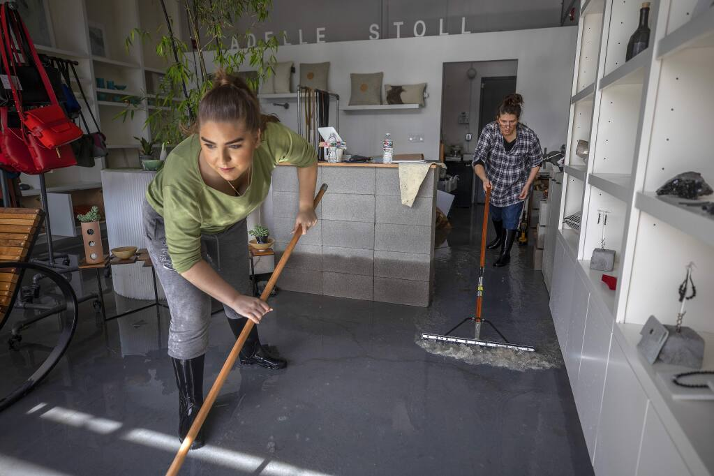 Valentina Stoll helps her mom Adelle squeegee water from her business, Adelle Stoll, in the Barlow business district in Sebastopol on Thursday. (John Burgess/The Press Democrat)