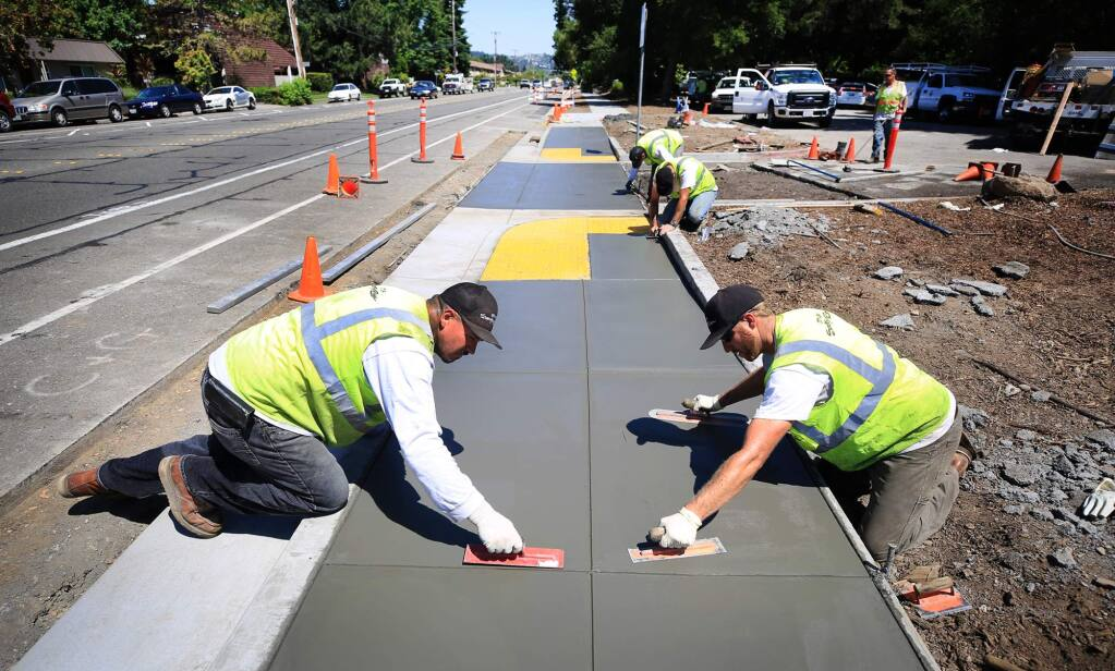 Santa Rosa city workers, Ramon Contreras, left, Josh Carstensen put the finishing touches on ADA accessible sidewalks fronting Howarth Park on Summerfield road in Santa Rosa, Tuesday June 20, 2017. (Kent Porter / Press Democrat) 2017