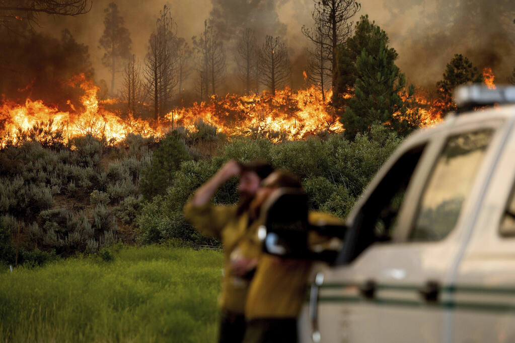 U.S. Forest Service firefighters Chris Voelker, left, and Kyle Jacobson monitor the Sugar Fire, part of the Beckwourth Complex Fire, burning in Plumas National Forest, Calif., on Friday, July 9, 2021. The Beckwourth Complex — a merging of two lightning-caused fires — headed into Saturday showing no sign of slowing its rush northeast from the Sierra Nevada forest region after doubling in size only a few days earlier. (AP Photo/Noah Berger)