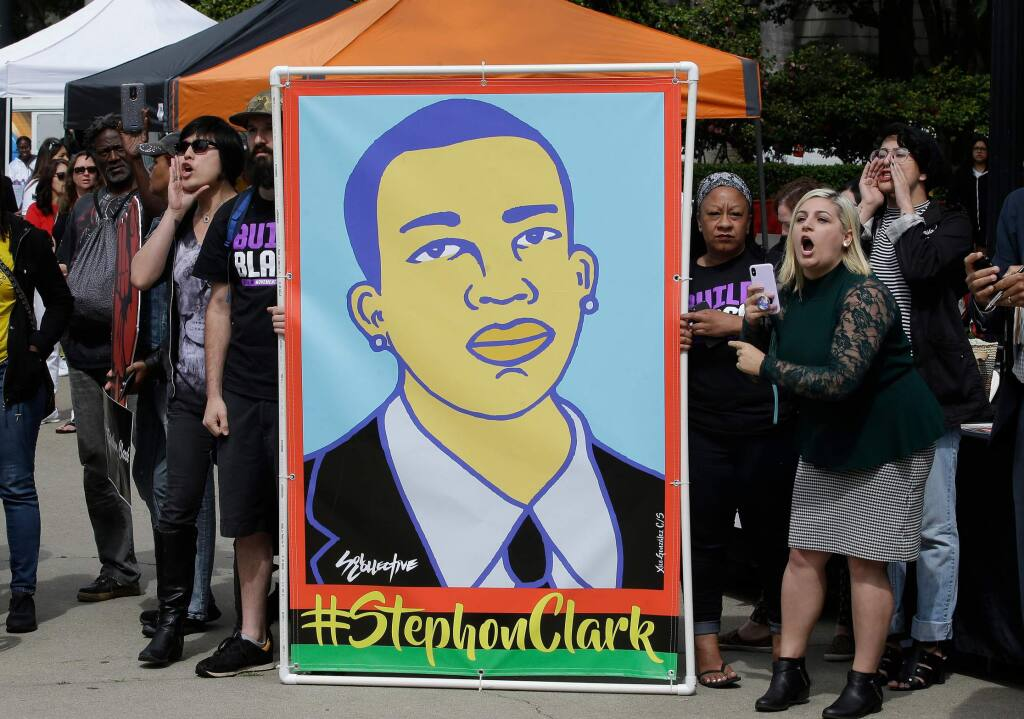 FILE - In this April 9, 2018 file photo protesters display an image of Stephon Clark at a crime victims rights rally, at the Capitol in Sacramento, Calif. Two Sacramento police officers won't face criminal charges for the fatal shooting of Clark following a chase that ended in his grandparents' yard and started a series of angry protests that roiled California's capital city, the county's top prosecutor announced Saturday, March 2, 2019, following a nearly yearlong investigation. (AP Photo/Rich Pedroncelli,File)