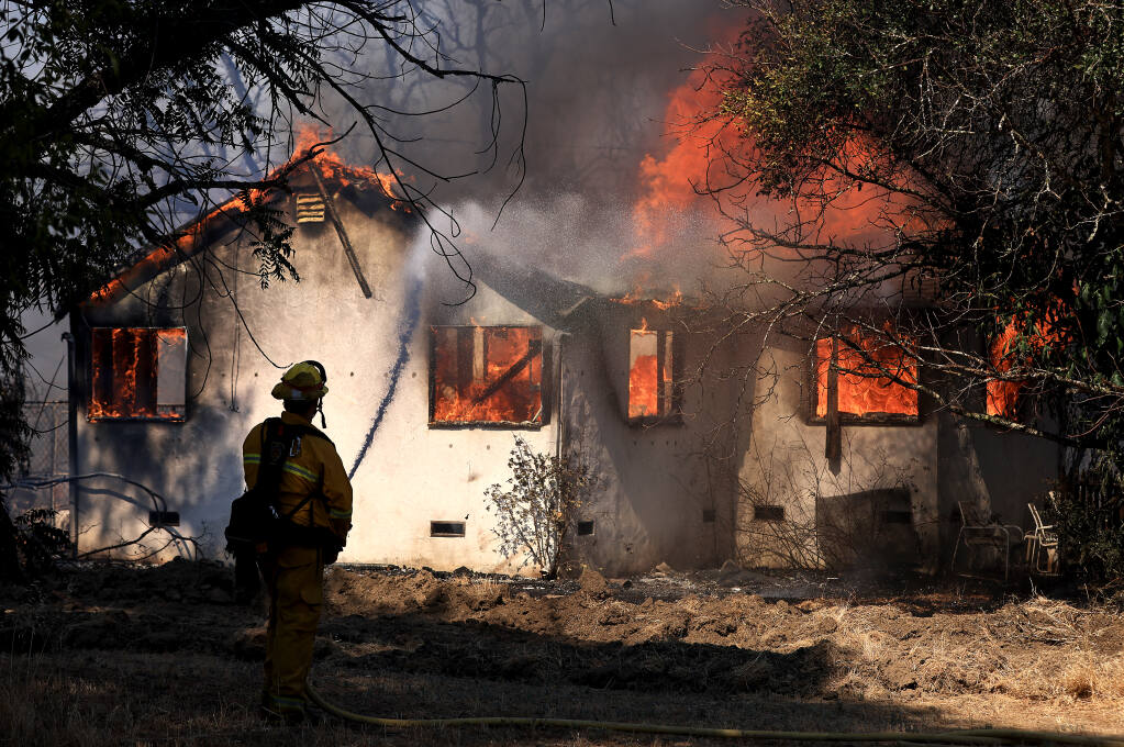 Firefighters take a defensive stand against a home burning on Forsythe Lane in Redwood Valley, ignited by an 80-acre wind-whipped brush fire, in tinder dry conditions, Wednesday, July 7, 2021.  (Kent Porter / The Press Democrat)