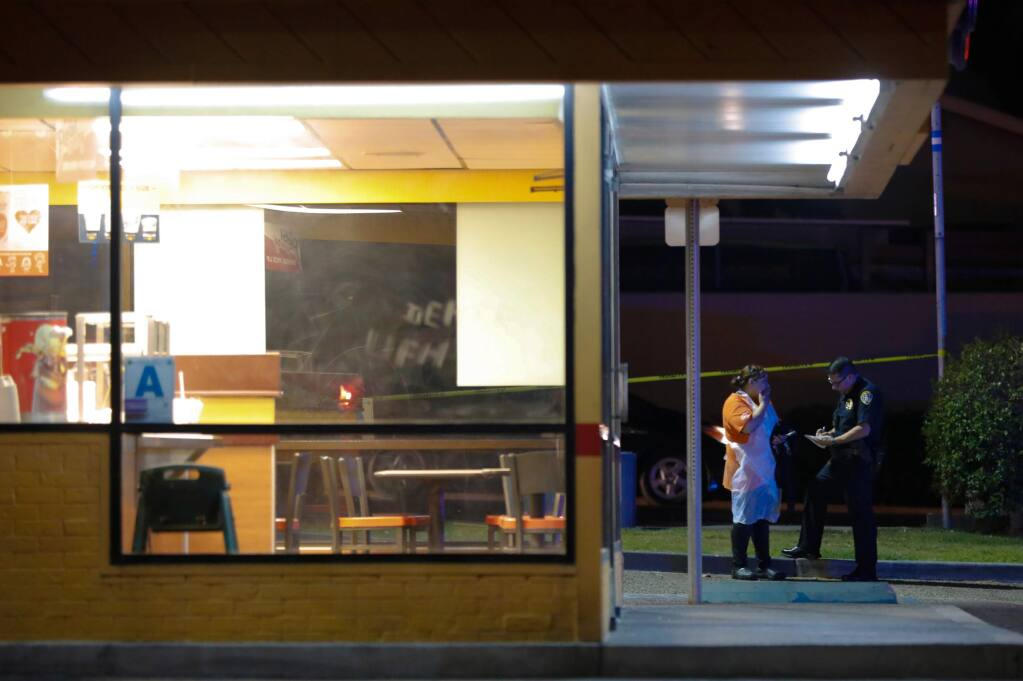 San Diego Police officers begin questioning witnesses after a shooting outside the Church's Chicken eatery in San Diego, Calif., Wednesday, Nov. 6, 2019. Authorities say the shooting happened Wednesday evening at a Church's Chicken in the Otay Mesa area. San Diego Police Officer John Buttle tells KNSD-TV the suspected gunman had been in the restaurant earlier in the day, when he tried to pay with a counterfeit bill. (Nelvin C. Cepeda/The San Diego Union-Tribune via AP)