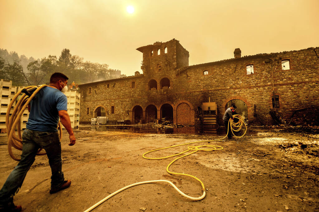 Winery workers Carlos Perez, left, and Jose Juan Perez extinguish hotspots at Castello di Amorosa, Monday, Sept. 28, 2020, in Calistoga, Calif., which was damaged in the Glass Fire. (AP Photo/Noah Berger)