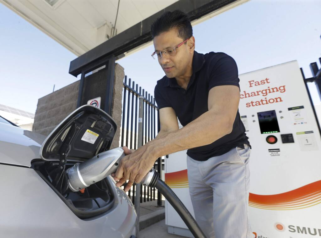 FILE - In this Sept. 17, 2015, file photo, Darshan Brahmbhatt, plugs a charger into his electric vehicle at the Sacramento Municipal Utility District charging station in Sacramento, Calif. (AP Photo/Rich Pedroncelli, File)