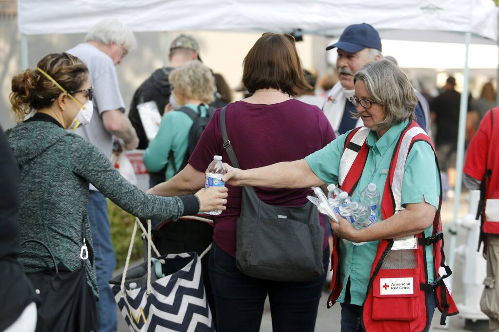 American Red Cross volunteer Sherrie Allen hands out water bottles at the FEMA hub at 427 Mendocino Ave in Santa Rosa, on Monday, October 16, 2017. (BETH SCHLANKER/ The Press Democrat)
