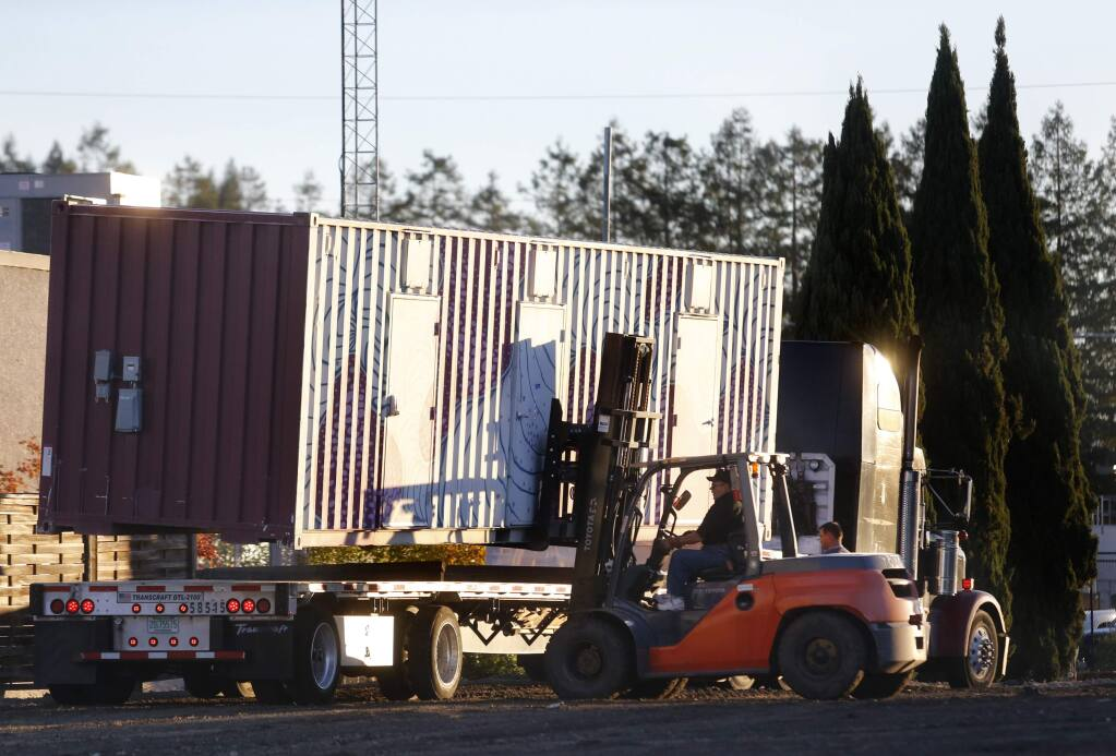 BETH SCHLANKER / The Press Democrat Glen Ghilotti of Team Ghilotti uses a forklift to unload a shipping container doubling as a temporary housing unit for an area called Oasis Village in Santa Rosa on Wednesday.