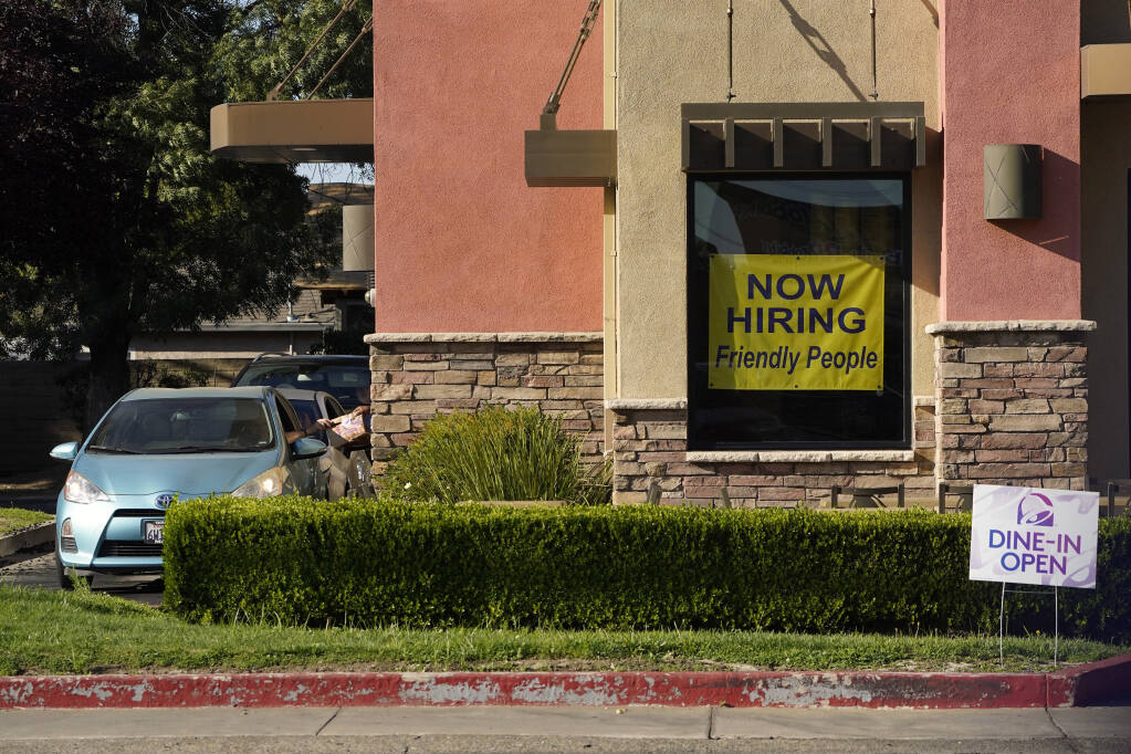 A hiring sign hangs in the window of a Taco Bell in Sacramento, Calif., Thursday, July 15, 2021. Hiring in California slowed down in June as the unemployment rate held steady at 7.7% according to new numbers released on Friday, July 16, 2021 by the Employment Development Department. California gained 73,000 jobs in June, ending the state's streak of four consecutive months of adding 100,000 jobs or more. But experts say the state is still struggling from a workforce shortage as California has added back just over half of the 2.7 million jobs it lost at the start of the pandemic.(AP Photo/Rich Pedroncelli))