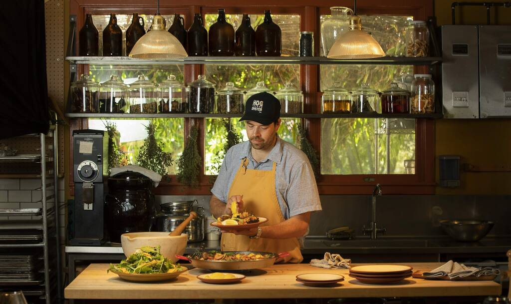 Chef Perry Hoffman serves up paella and a green salad in the kitchen at the Boonville Hotel in the Anderson Valley. (John Burgess/The Press Democrat)