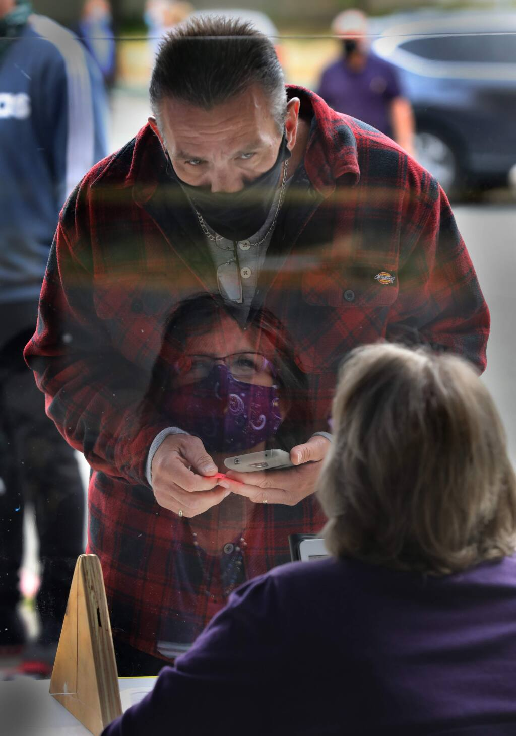 Robert Borders goes through the screening process for COVID-19 with Sonoma County Court worker Dawn P. outside the Sonoma County Superior Court in Santa Rosa, Calif., on Monday, June 1, 2020. (BETH SCHLANKER/ The Press Democrat)