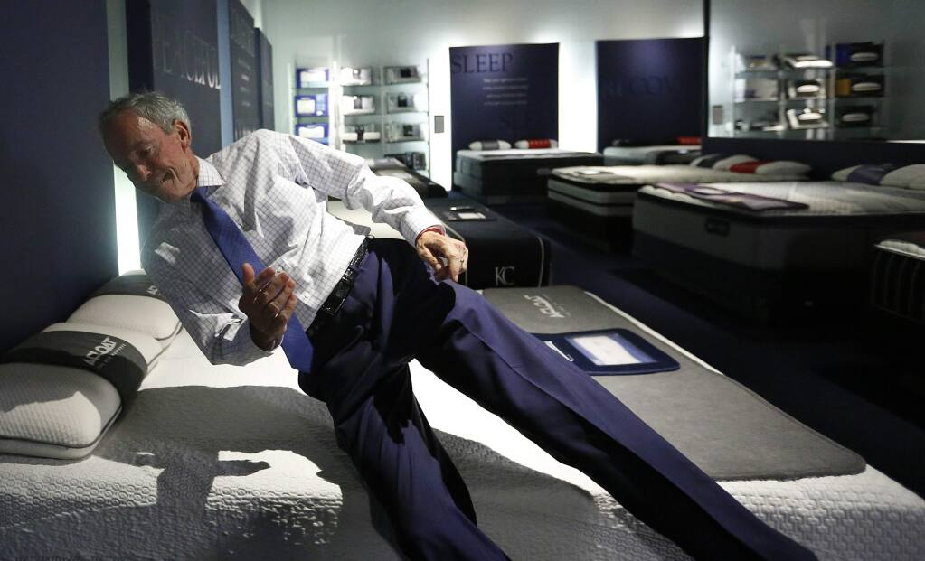 In this June 26, 2018, photo City Furniture CEO Keith Koenig, jumps onto a waterbed as he speaks during an interview with the Associated Press, in Tamarac, Fla. Koenig and inventor Charles Hall, pioneers of the waterbed industry in the United States, are hoping to generate a new wave of popularity for the old furniture concept by using a wholesome new pitch. (AP Photo/Brynn Anderson)