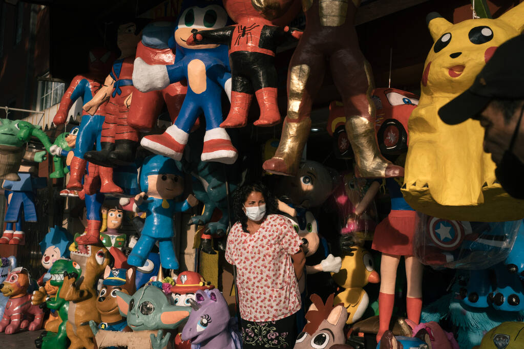 Maricela Ortega among the piñatas at her husband's piñata shop in Mexico City, on March 31, 2021. The piñata industry, dependent on social gatherings, has seen sales plummet. Some artisans, in a creative bid to survive, have added coronavirus figures to their lineups of superheros and princesses. (Luis Antonio Rojas/The New York Times)