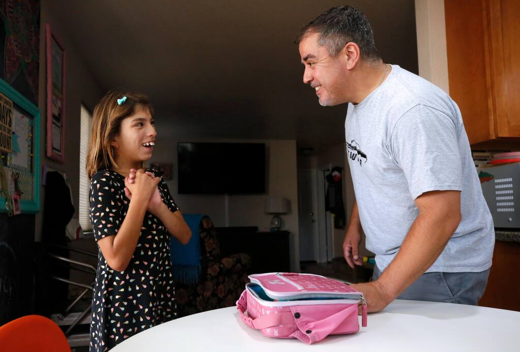 Gigi Rocha, 11, laughs with her father Jose at their home in Windsor, California, on Saturday, August 1, 2020. Distance learning brought on by the COVID-19 pandemic poses a challenge to families with children who have special needs. (Alvin A.H. Jornada / The Press Democrat)