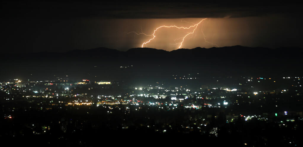 Lightning bolts, Sunday, Aug. 16, 2020, strike out over the coast before moving inland over Santa Rosa. (Kent Porter / The Press Democrat) 2020