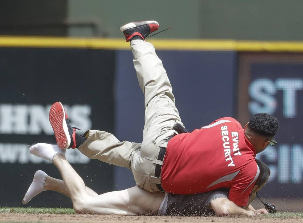 A security guard tackles a fan that ran on the field during the second inning of a baseball game between the Milwaukee Brewers and the San Francisco Giants Thursday, June 8, 2017, in Milwaukee. (AP Photo/Morry Gash)