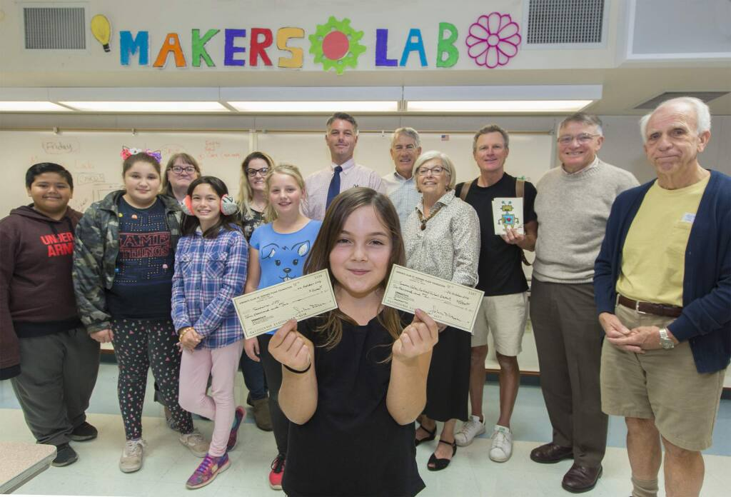 Student Eva Rose Logizerio, 10, holds two checks that total $26,000, which will be used to create a Maker Lab at Sassarini Elementary School. The funds were donated by the Kiwanis of Sonoma Plaza. (Photo by Robbi Pengelly/Index-Tribune)