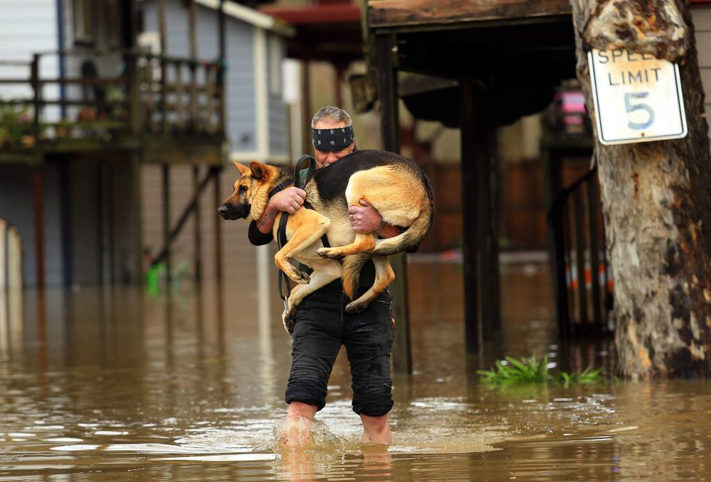 Jeremiah Dock carries his dog, Sergeant , from his home in the Sycamore Court Apartments on Church St. as the Russian River crested in Guerneville on Monday morning, January 9, 2017. (John Burgess/The Press Democrat)