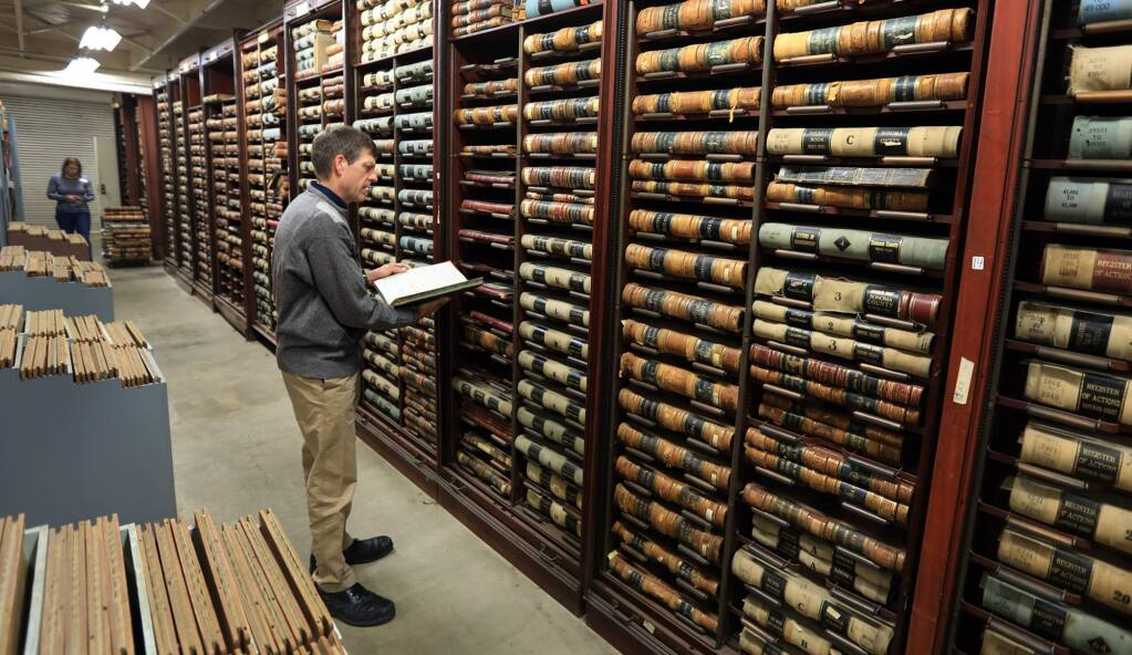 Geoffrey Skinner a cataloging and metadata librarian and Katherine Rinehart, manager of the History and Genealogy of the Sonoma County Library, look over the condition of Sonoma county's historical archive housed on the campus of Los Guilicos past women's detention center, Tuesday Nov. 14, 2017. The October fires came perilously close to the entire campus and archives . (Kent Porter / The Press Democrat