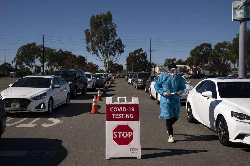 Student nurse Ryan Eachus collects forms as cars line up for COVID-19 testing at a testing site set up the Orange County Fairgrounds in Costa Mesa on Nov. 16, 2020. (Jae C. Hong, / Associated Press)