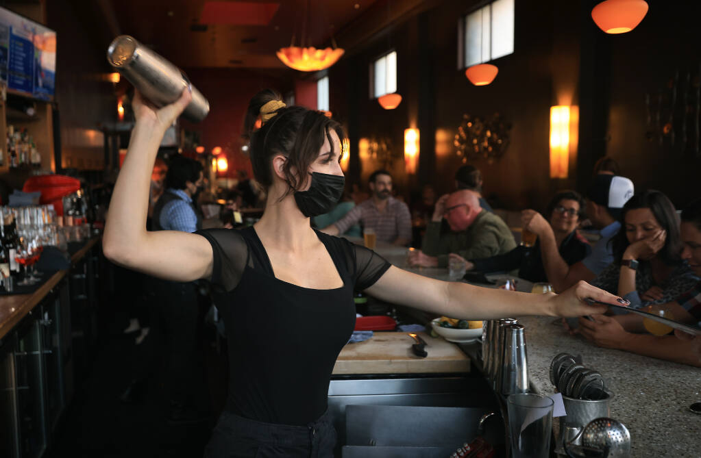 Jackson's Bar and Oven bartender Jaycie Mariani mixes a drink while handing out a menu during the evening dinner rush, Friday, Sept. 17, 2021 in Santa Rosa.   (Kent Porter / The Press Democrat) 2021