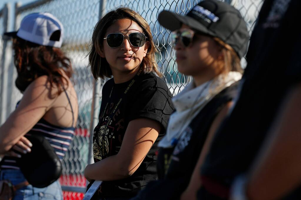 Pro Stock motorcycle drag racer Jianna Salinas, second from left, looks down the track while waiting for her father, Top Fuel driver Mike Salinas, to take the starting line during the nitro qualifying session in the NHRA Sonoma Nationals at Sonoma Raceway on Friday, July 26, 2019. (Alvin Jornada / The Press Democrat)
