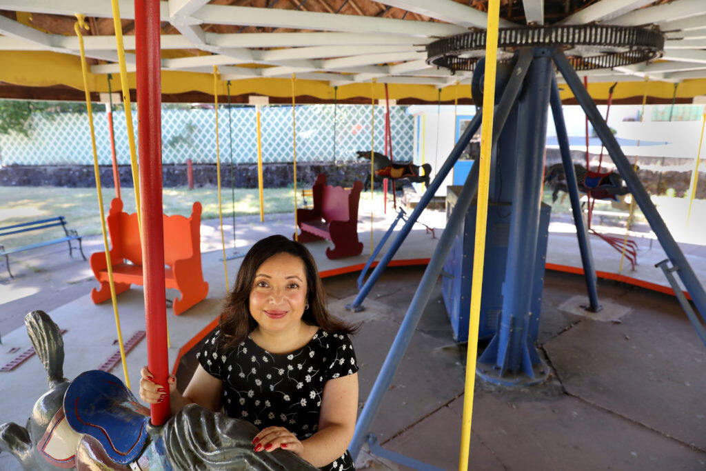 """Filmmaker Malinalli Lopez Arreguin, on the carousel at the now closed Sonoma Developmental Center in Glen Ellen  on Wednesday, July 10, 2019. Her documentary """"True Humans"""" premiers on Aug. 4th at the Sebastiani Theater. (BETH SCHLANKER/ The Press Democrat)"""