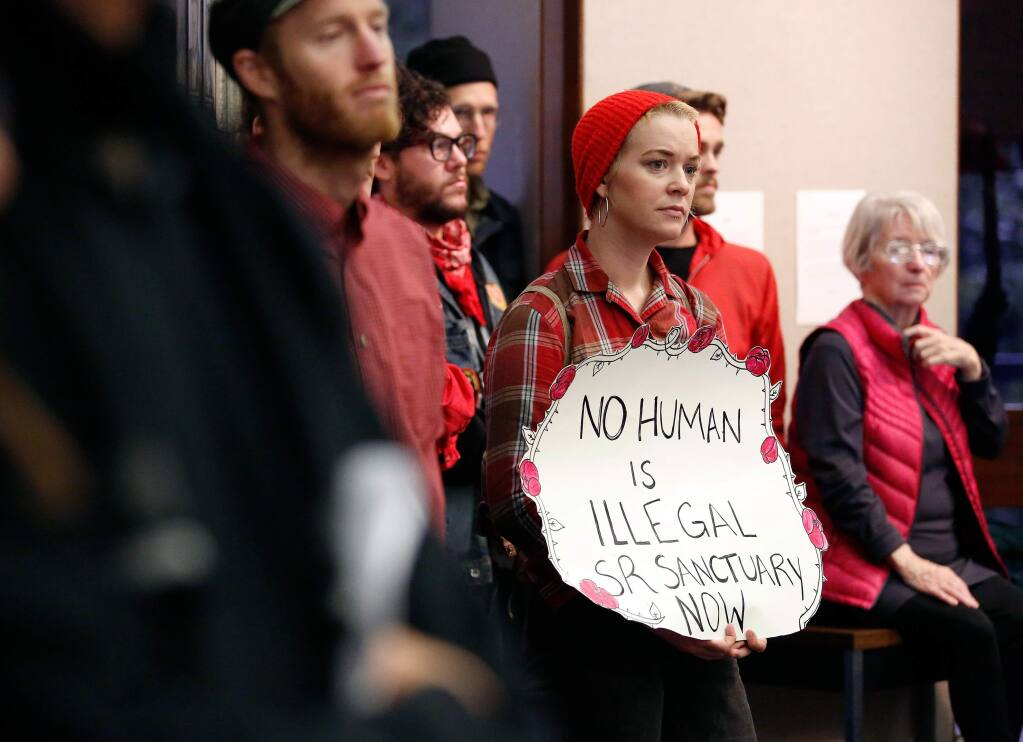 Quenby Dolgushkin holds a sign in support of making Santa Rosa a sanctuary city during a city council meeting to discuss a proposal giving safe haven to undocumented immigrants in Santa Rosa, California on Tuesday, Feb. 7, 2017. (Alvin Jornada / The Press Democrat)