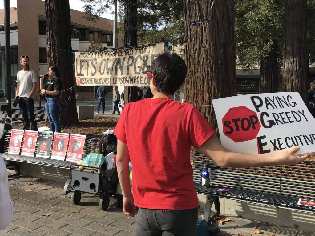 Russ Aguilar, right, holds a sign critical of PG&E while Alba Diaz translates J.D. Opperman's remarks into Spanish at a rally organized by the North Bay chapter of the Democratic Socialists of America on Saturday, Nov. 16, 2019, at Old Courthouse Square in Santa Rosa. (Will Schmitt/The Press Democrat)