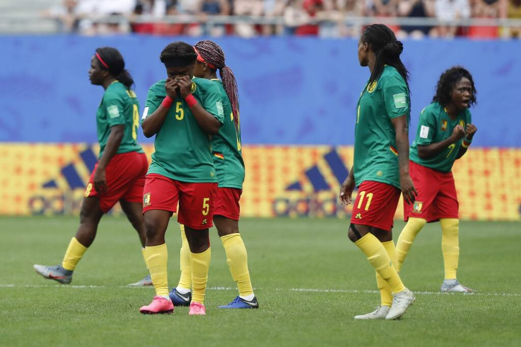 Cameron players react after a VAR decision that ruled out Ajara Nchout's goal for offside during the Women's World Cup game between England and Cameroon at the Stade du Hainaut stadium in Valenciennes, France, Sunday, June 23, 2019. (AP Photo/Michel Spingler)