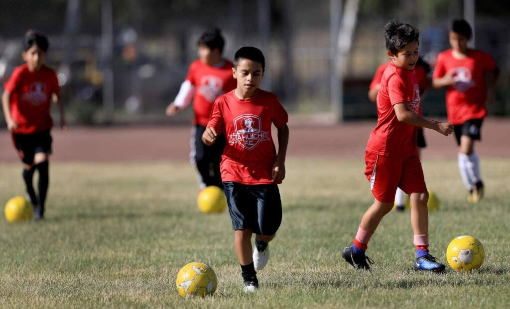 The Tahuichi Soccer Club's U8 boys participate in dribble drills during the team's practice on the athletic fields of Elsie Allen High School, Thursday June 14, 2018 in Santa Rosa. (Kent Porter / The Press Democrat) 2018