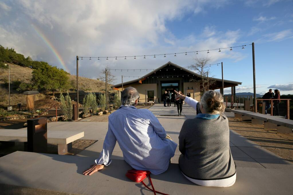 Former property manager Fernando Marquez and friend Marleen Mulder, who both lost their residences during the Tubbs Fire, sit outside and enjoy a rainbow during the grand reopening party of Paradise Ridge Winery in Santa Rosa on Sunday, December 8, 2019. (BETH SCHLANKER/ The Press Democrat)