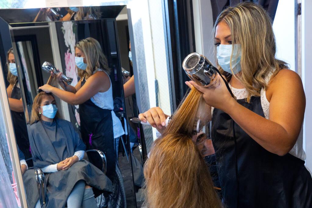 Hairdresser Adriana Wilson blow-dries Michelle Lifto's hair at the Powder Room salon in Santa Rosa on Saturday, Oct. 24, 2020. (Alvin A.H. Jornada / The Press Democrat)