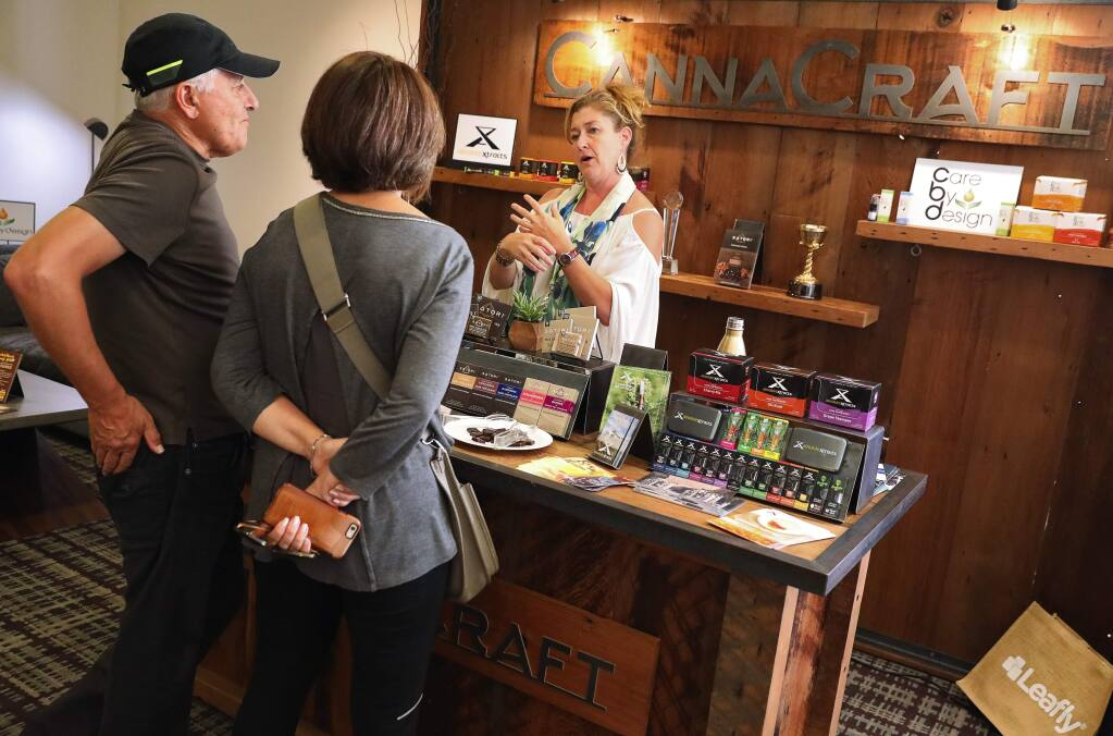 Melanie King, right, with CannaCraft, talks to Maryam and Majid Rahimian about cannabis products, during the Wine & Weed Symposium, in Santa Rosa on Thursday, August 3, 2017. (Christopher Chung/ The Press Democrat)