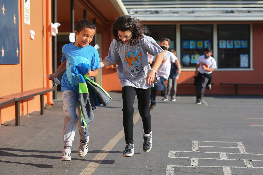 Third-graders Dylan Armanino, left, and Eliana Olvera race around the playground at Proctor Terrace Elementary School as part of the iDo26.2 running program in Santa Rosa on Friday, Sept. 24, 2021.  (Christopher Chung/ The Press Democrat)