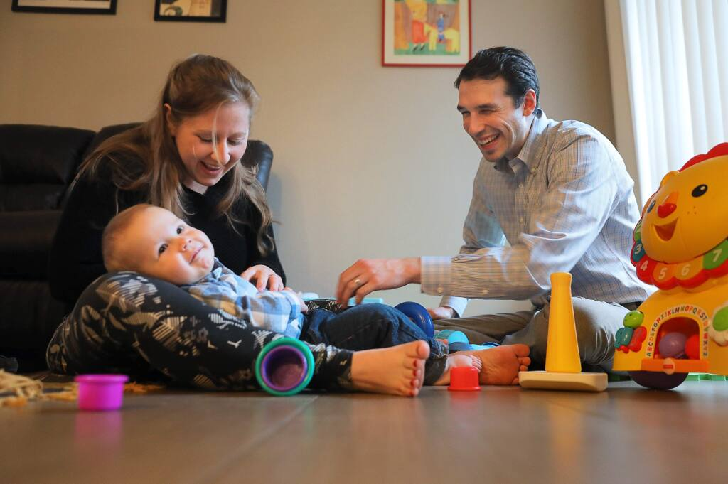 Santa Rosa High School teacher Nightsnow Vogt, right, and his wife, Melissa, play with their 13-month-old son, Camilo, in their Santa Rosa apartment on Tuesday, February 26, 2019. (Christopher Chung/ The Press Democrat)