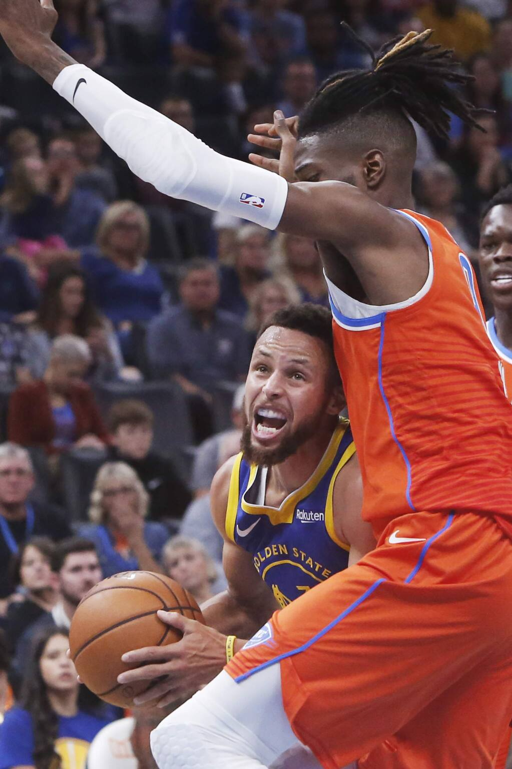 Golden State Warriors guard Stephen Curry, left, drives against Oklahoma City Thunder forward Nerlens Noel in the first half of an NBA basketball game Sunday, Oct. 27, 2019, in Oklahoma City. (AP Photo/Sue Ogrocki)